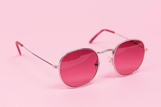 ピンクの背景にピンクのサングラス。ピンクで孤立。ファッションとスタイル