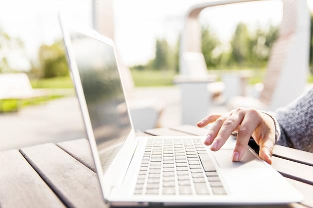 ラップトップキーボードを手でクリック。公園のテーブルに手とノートブック