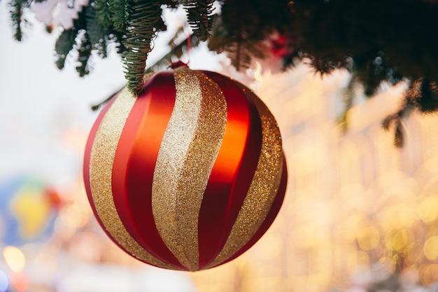 クリスマスツリーの緑の枝に大きな赤い新年ボール