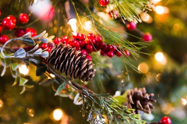 クリスマスツリーの緑の枝に黄色のライトが付いている円錐形。お正月飾り