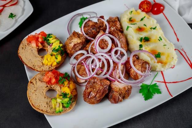 テーブルの上の皿にマッシュポテト焼き串焼き豚肉のグリル