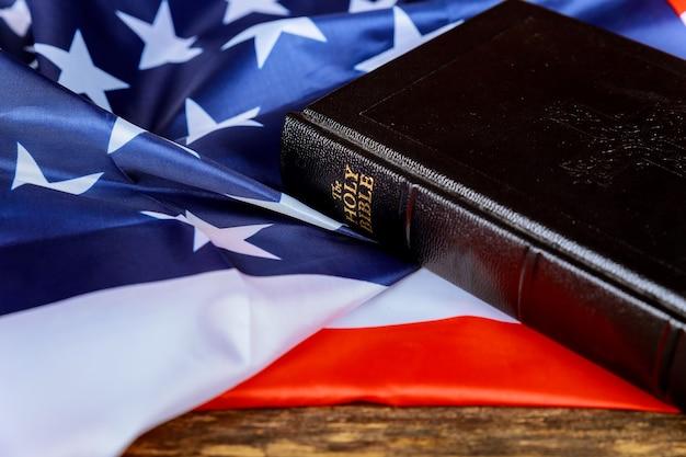 アメリカ合衆国の国旗と苦しめられた木製の背景に聖書