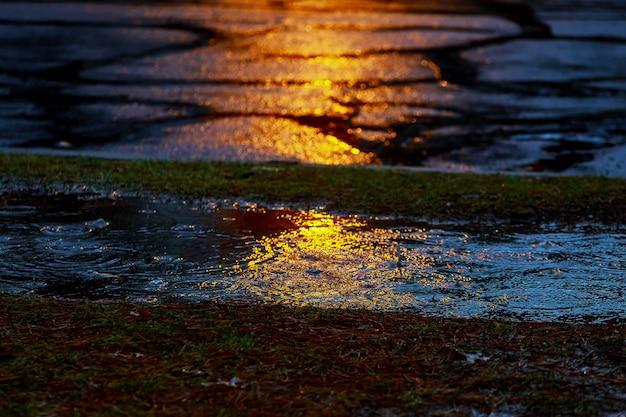 ぬれたアスファルトの上の反射と雨の後の通り