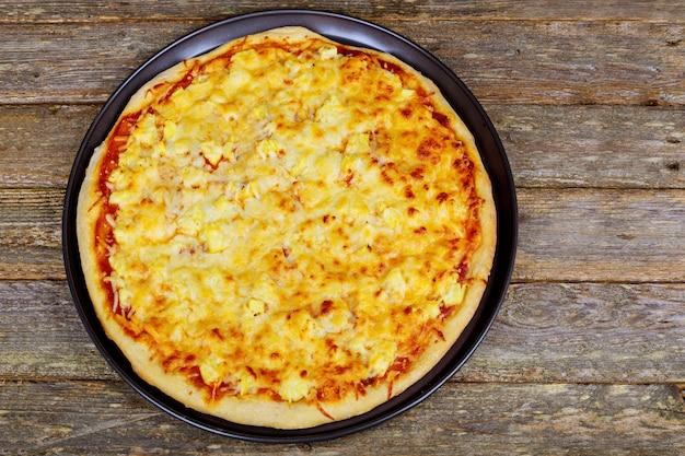 ペパロニ、モッツァレラチーズ、トマトソースのアメリカンピザ。木製のテーブルの上のピザ