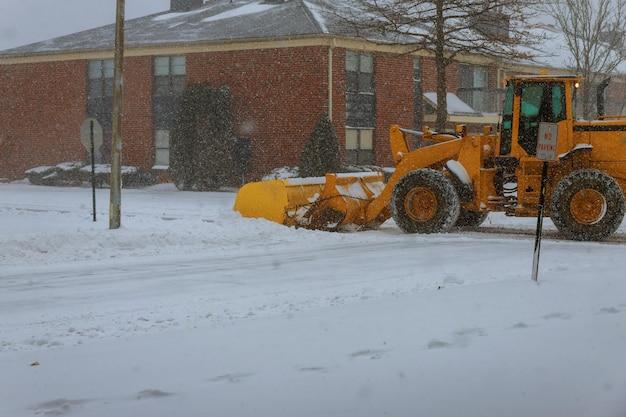 雪の嵐の中で街の通りを掃除除雪トラック