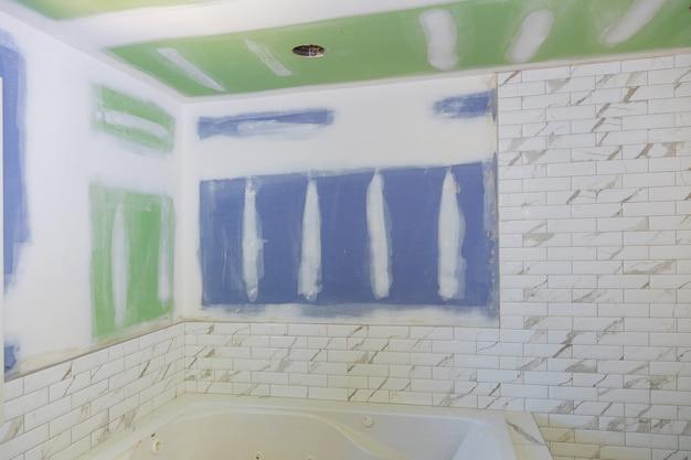 乾式壁と修繕の新しい工事中のバスルームのインテリア