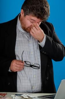Бизнесмен, снимая очки, чувствует усталость глаз, массируя сухие глаза после длительного использования ноутбука
