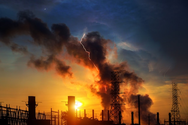 工場 - 石油およびガス産業劇的な空の夕焼けと稲妻