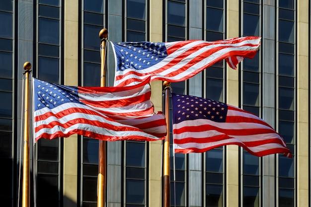 Американский флаг развевается на ветру на фоне здания.