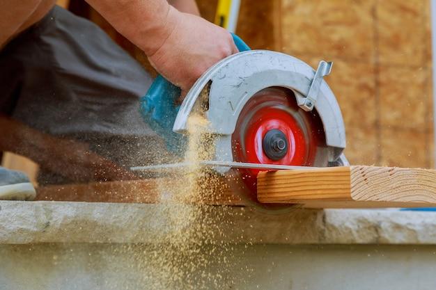 丸鋸を使用して大規模な木の板をカットする大工のクローズアップ