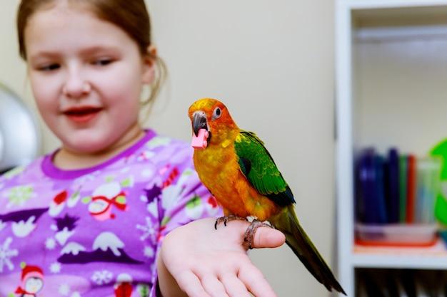 小さな女の子はオウムの手を握る