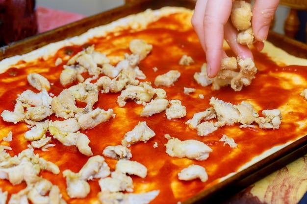 女性が台所でピザを準備します。