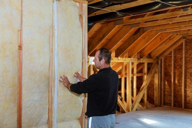 ミネラルウールを使用して住宅の屋根裏を断熱する労働者