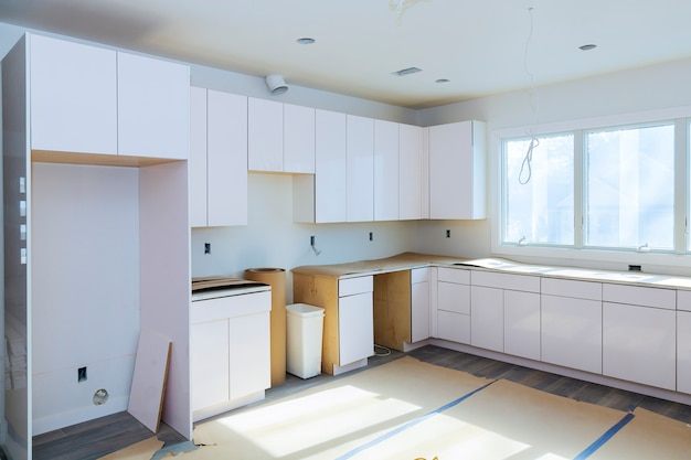 モダンなキッチンキッチンに新しいコンロを取り付けるキッチンキャビネットを取り付けます。