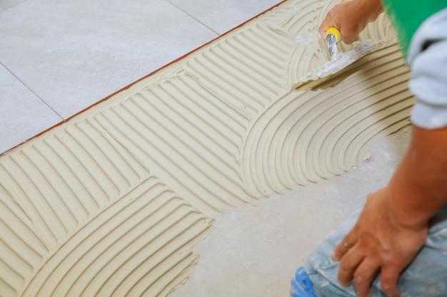 バスルームの床にタイルを貼り付ける前に、湿ったモルタルを広げます。接着剤を入れる