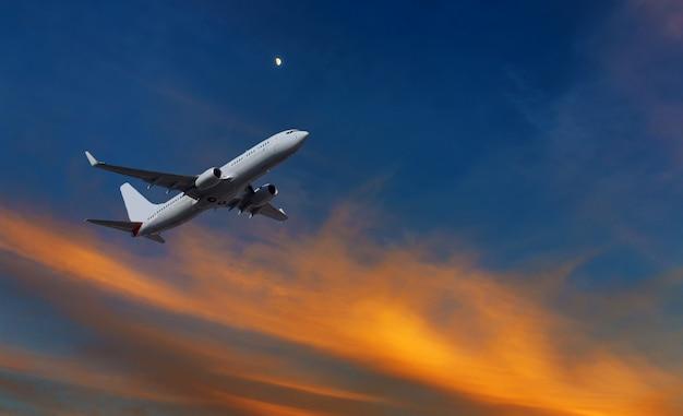 日没のオレンジと黄色で離陸後の商業飛行機の登山