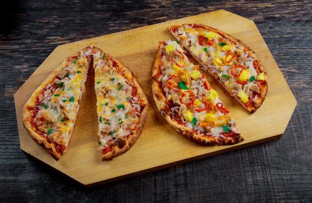 暗い背景においしい新鮮なピザをスライスします。木製のテーブルの上のピザ