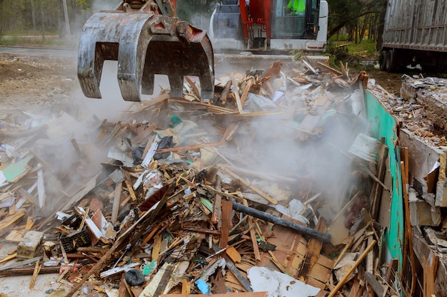 Экскаватор разбирает сломанный дом после трагедии