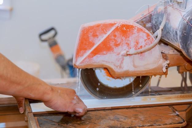 タイルを切断するための特別な機械でのセラミックタイルの手動切断。