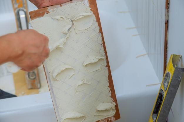 建設用メイソン男の手がセメントモルタルで動作するタイル