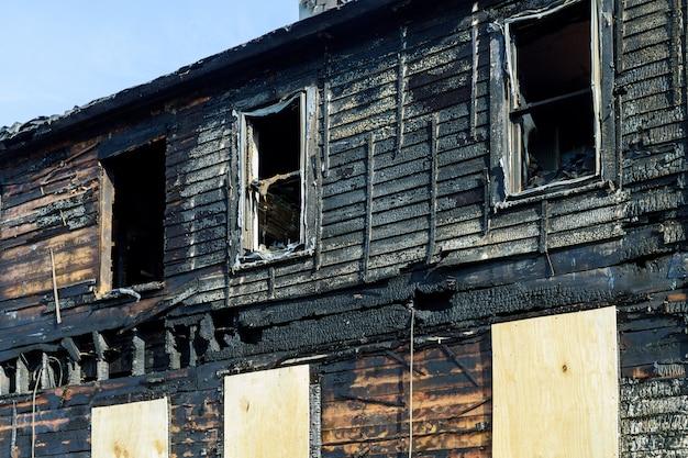 破壊された家の前の消防車。焼けた家