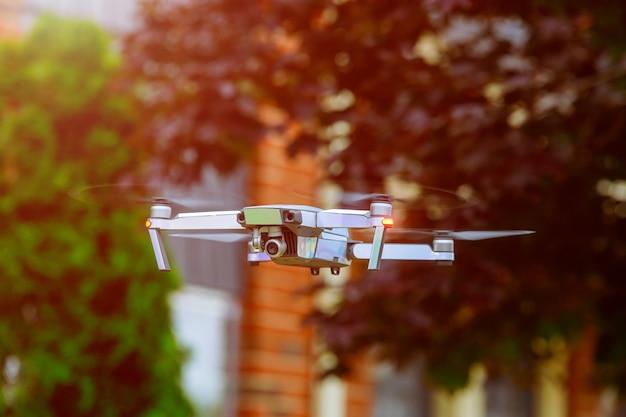 夕暮れの街の上を飛んでいる無人機