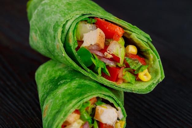 ブリトーは牛肉と野菜の黒の背景に包みます。ビーフブリトー、メキシコ料理。