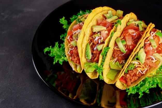 木製の背景に黒い皿においしいタコスの新鮮な野菜
