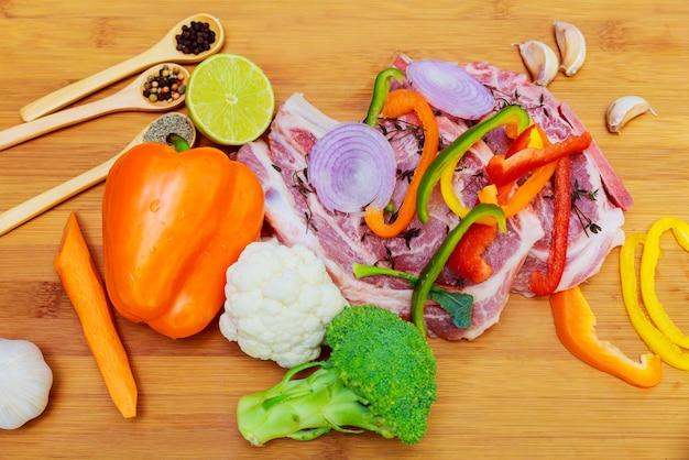 トマトの枝、肉と調味料の境界線のナイフでまな板の上のマリネ、生豚肉テキスト木製素朴な背景のトップビュー