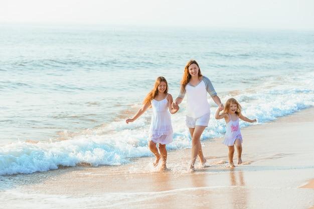 Семья гуляя на пляж вечера во время захода солнца.