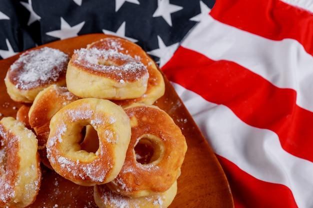 木製の皿にアメリカの独立記念日、お祝いのドーナツとアメリカの国旗