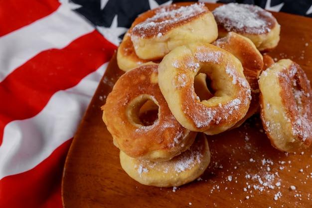 アメリカの国旗の背景の上においしい緑豊かなドーナツのクローズアップ