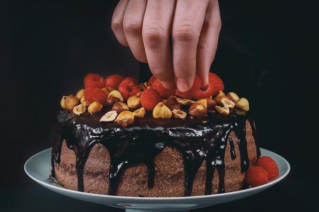 Шеф-кондитер на кухне украшает шоколадный торт с малиной