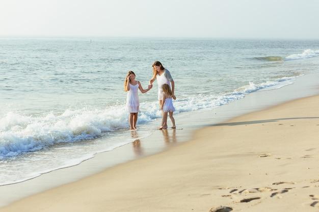 日没時に夜のビーチを歩く家族。