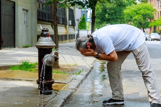強い暑さの中の男は消火栓の水でリフレッシュされます