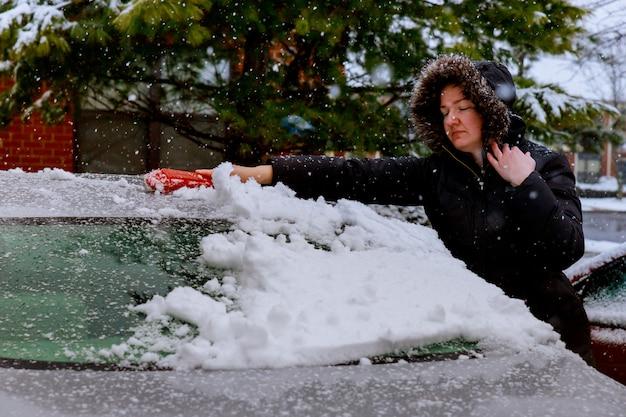 若い女性は彼女の車から雪を一掃します。