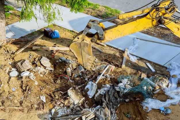 Экскаватор работает на мусорной свалке при загрязнении почвы.