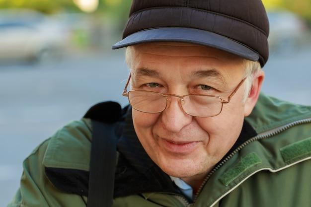 屋外に立ってカメラを見て魅力的な年配の男性のクローズアップの肖像画