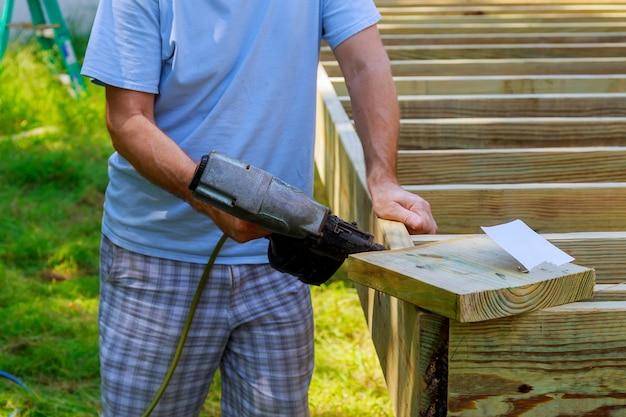 Рабочий, устанавливающий деревянный пол для внутреннего дворика