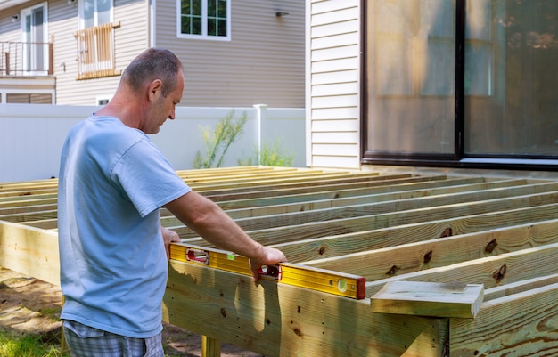 ハンマーで一緒にねじ込みで木製のパティオを構築する男