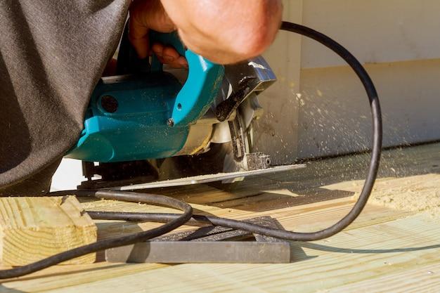 Красавец плотник с помощью циркулярной пилы установка деревянный пол на открытой террасе