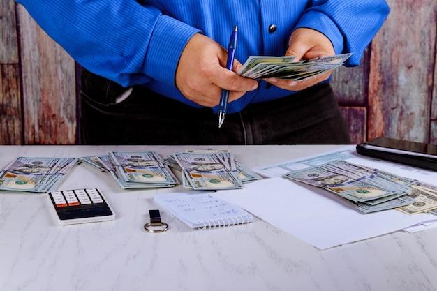 手はドルを数えます。その男はそのお金を数える。新しい百ドル札