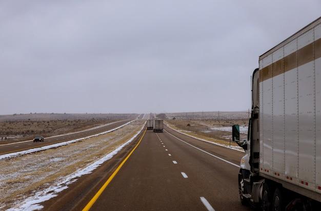 アメリカのニューメキシコ州の雪に覆われた未舗装の道路を走行する野生のトラック