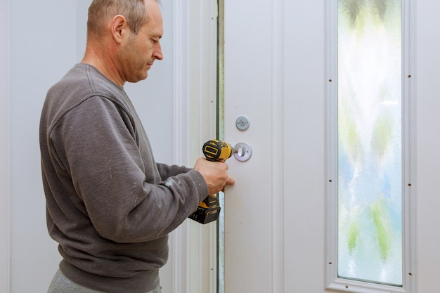 取り付けは室内ドアのノブをロックし、クローズアップの木工師の手はロックを取り付けます。