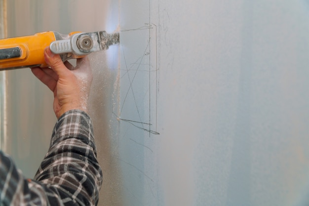 電気カッターアングルグラインダーを使用して石膏ボードを切断建設労働者