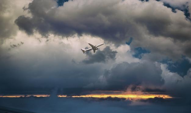 飛行中の白い旅客機。飛行機は夕焼け雲に逆らって飛ぶ。航空機の側面図です。