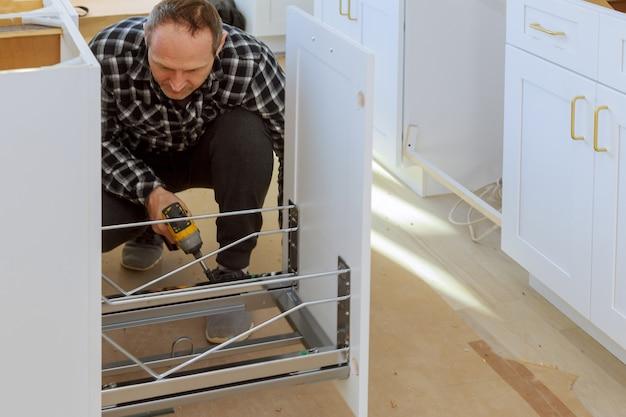 大工は台所で引き出しのゴミ箱を構築しています