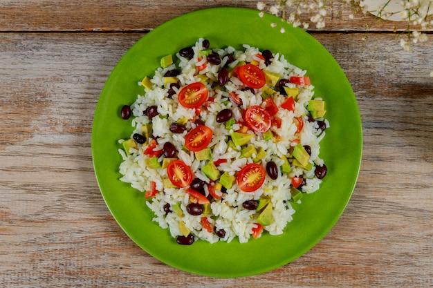 Здоровый зеленый вегетарианский обед с рисом, помидорами, авокадо на столе.