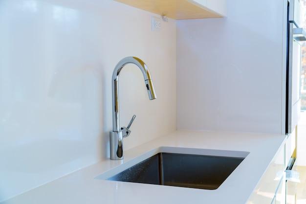 Новая современная белая кухня со встроенным хромированным краном