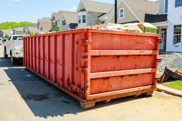 新しい家の近くのゴミ容器、赤い容器、リサイクルおよび廃棄物建設の背景